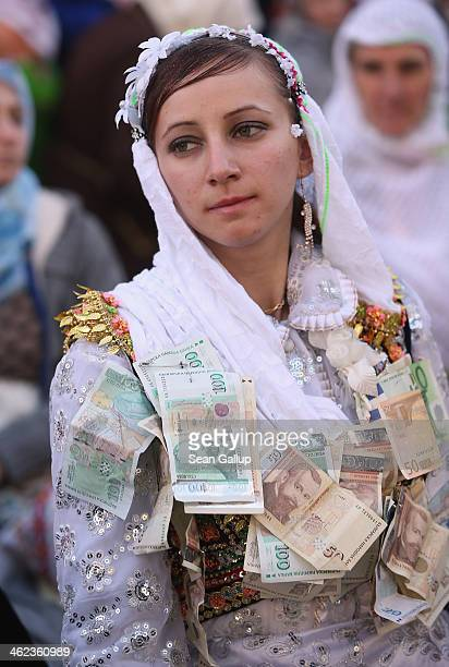 Bride Fatme Inus her clothes pinned with money received from friends and relatives participate in a group dance on the main square where hundreds of...