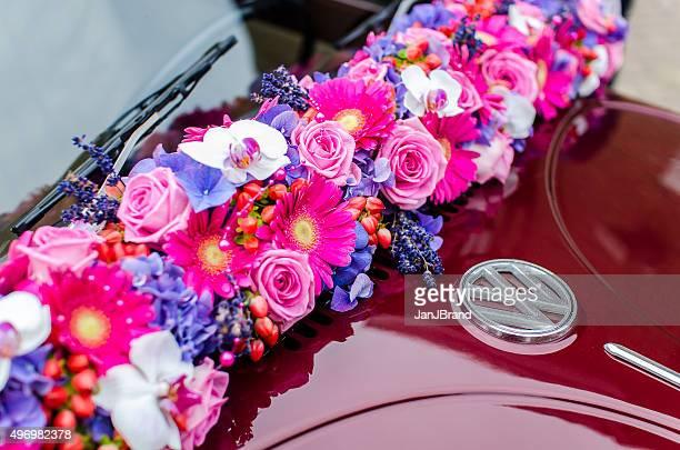 Braut und Blumen auf einem VW Käfer