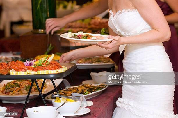 bride getting food from buffet.  - dean foods stock photos and pictures