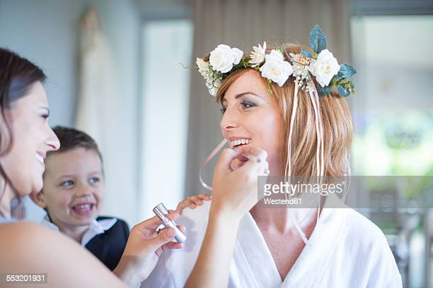 Bride getting ready for wedding with bridesmaid