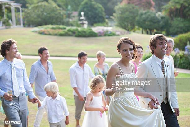 Bride, groom and guests walking across lawn