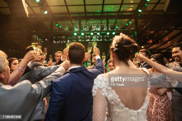 bride, groom and wedding guests making a toast - wedding stock pictures, royalty-free photos & images