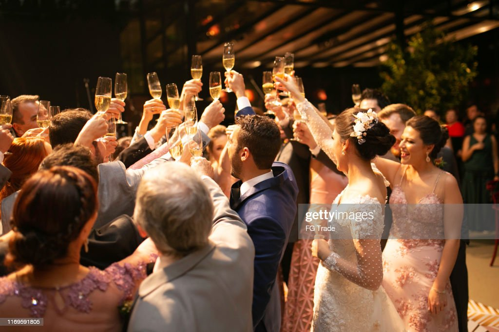 Bride, groom and wedding guests making a toast : Stock Photo