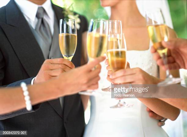 Bride, groom and wedding guests toasting with champagne, mid section