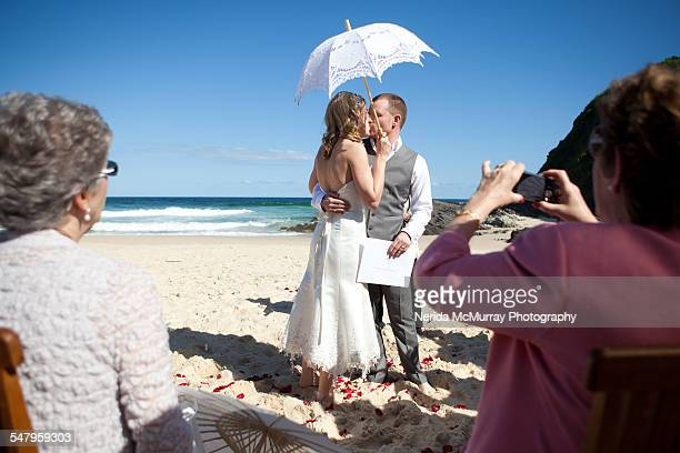 Bride & Groom kiss during ceremony on beach