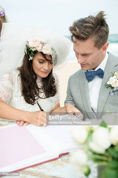 bride & groom signing marriage certificate - register stock photos and pictures