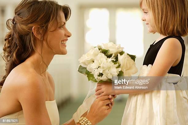 Bride handing bouquet to flower girl