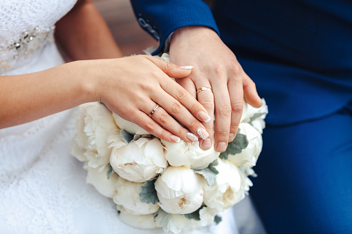 Bride hands with ring and wedding bouquet of flowers 868470354