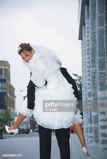 Bride having piggyback ride,  looking over shoulder, smiling, portrait