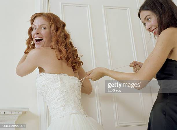 Bride having wedding dress laced up by young woman, smiling