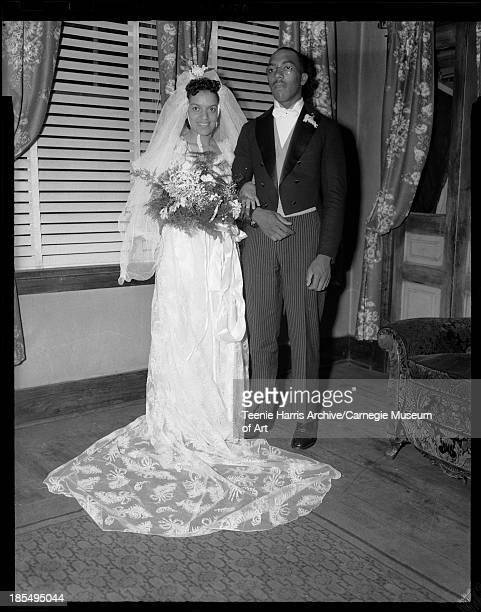 Bride Helen L Brown Jefferson wearing gown with sheer feather pattern and long train and groom Willard M Jefferson posed in interior with venetian...