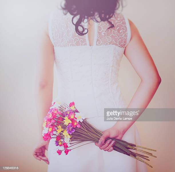 Bride hiding bouquet of flowers behind her back