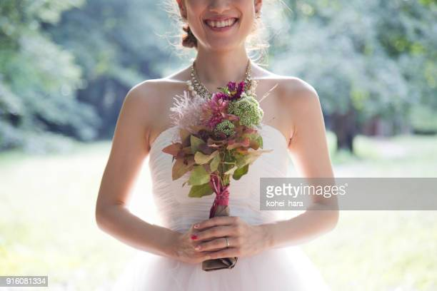 bride holding a bouquet in the park - wedding ceremony stock pictures, royalty-free photos & images