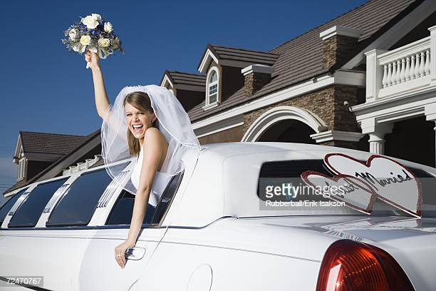 A bride holding a bouquet of flowers and leaning out of a limo window