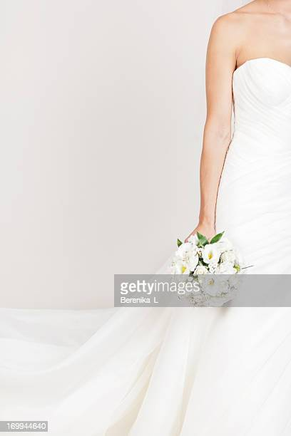 bride holding a bouquet - wedding dress stock pictures, royalty-free photos & images
