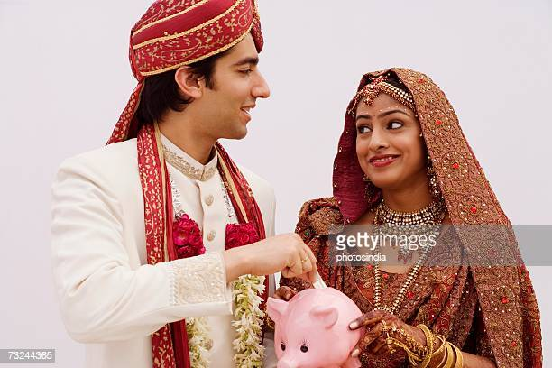 Bride holding a piggy bank with a groom putting money in it