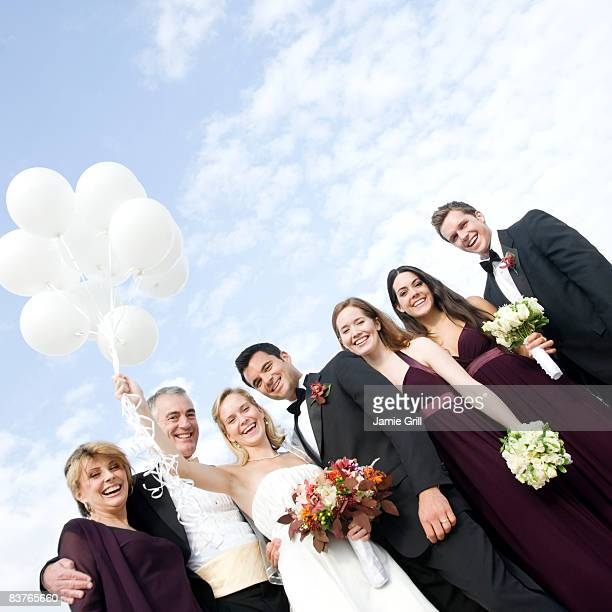 Bride holding balloons with bridal party outside