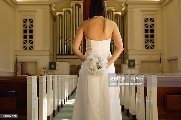 bride holding bouquet behind back - strapless dress stock pictures, royalty-free photos & images