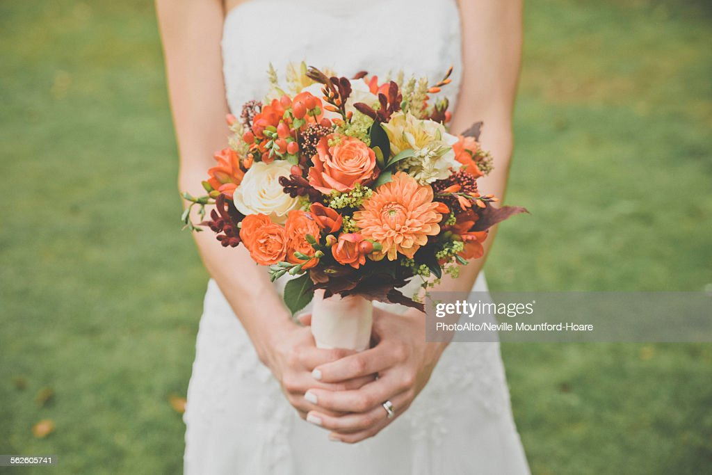 Bride holding bouquet, cropped : Stock Photo