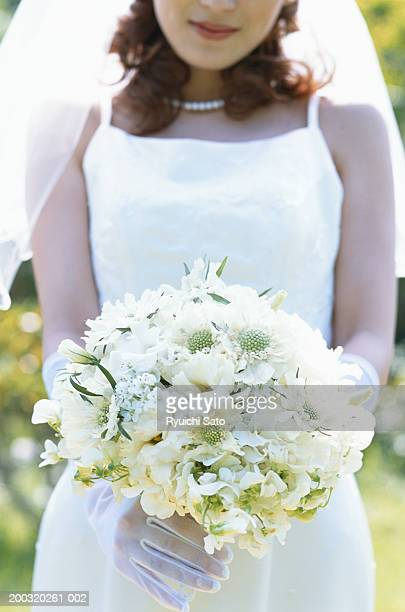 Bride holding bouquet, mid section