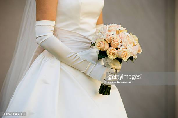 Bride holding bouquet, mid section, side view