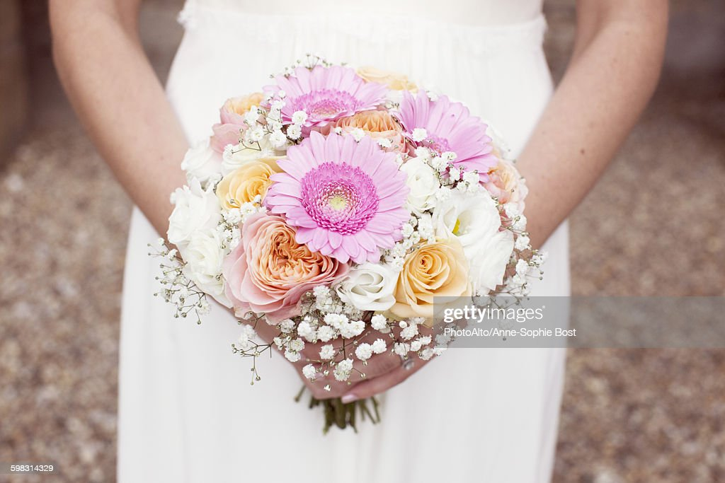 Bride holding bouquet of flowers, cropped : Stock Photo