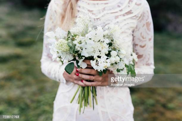 bride holding bouquet - lace dress stock pictures, royalty-free photos & images