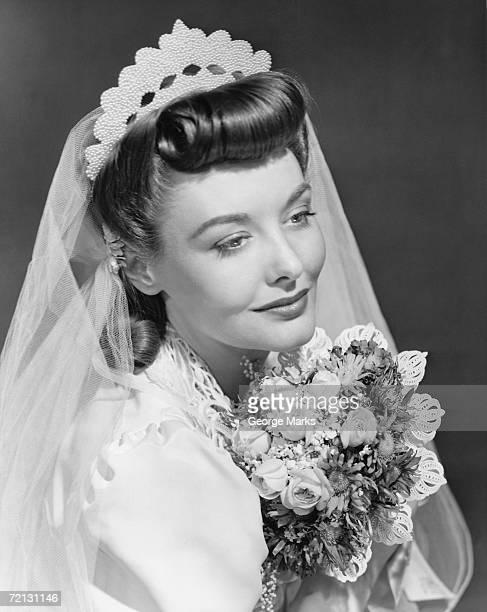Bride holding bouquet, posing in studio (B&W),, portrait