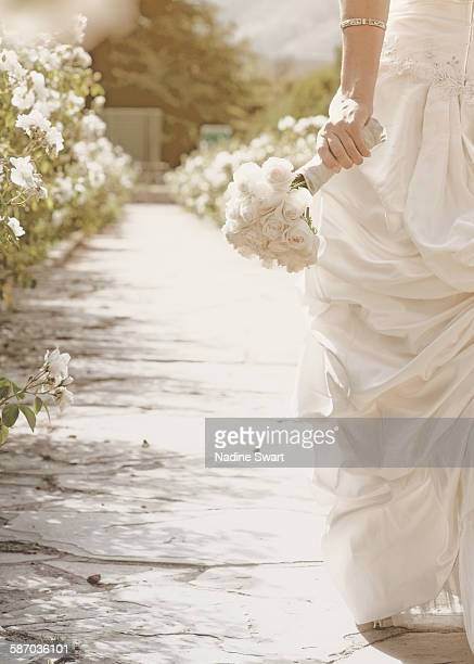 Bride holding bouquet walking down a path