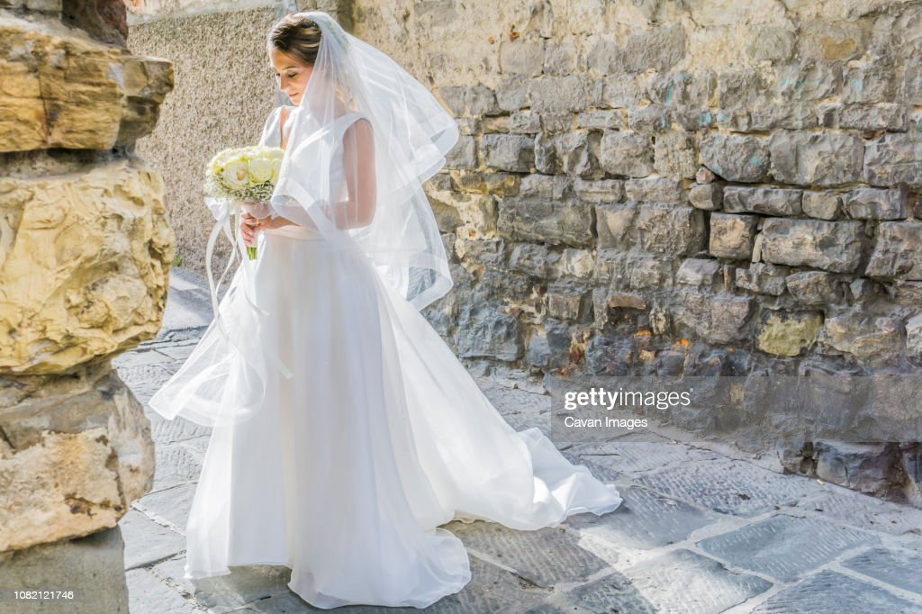 Bride holding bouquet while standing at alley against wall : ストックフォト