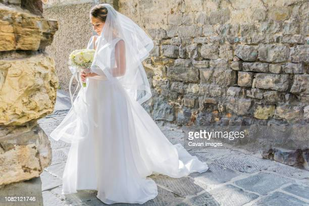 bride holding bouquet while standing at alley against wall - ベール ストックフォトと画像