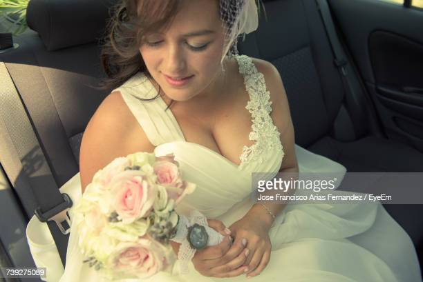 bride holding bouquet while traveling in car - escote fotografías e imágenes de stock