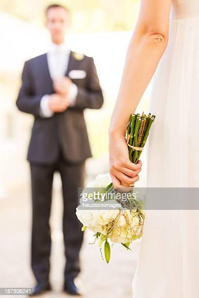 Braut Holding Blumenstrauß und Bräutigam stehen im Hintergrund