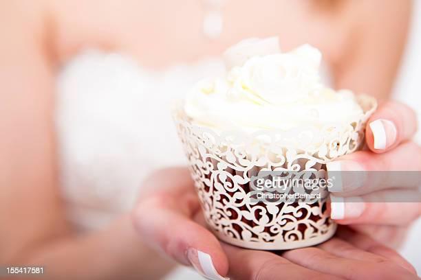 Bride holding wedding cupcake