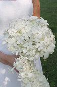 bride holding white flowered wedding bouquet