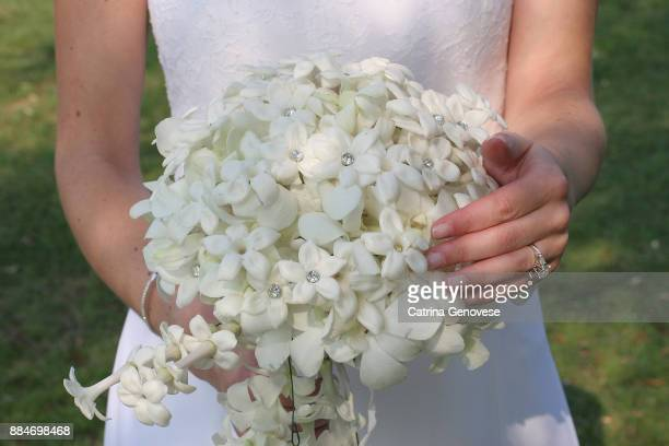 bride holding white flowered wedding bouquet