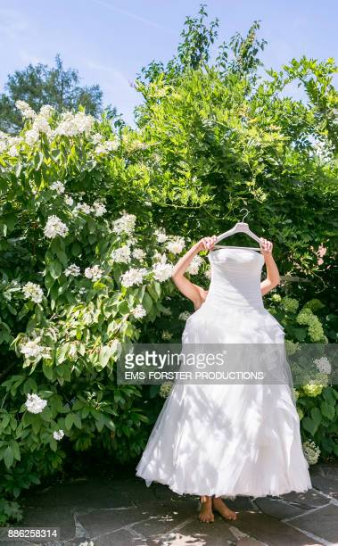 bride holding white wedding dress in front of green plants