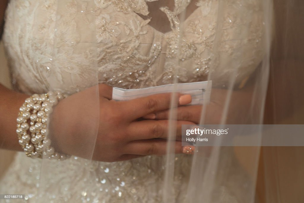 Bride holding written vows, hands clasped : Stock Photo
