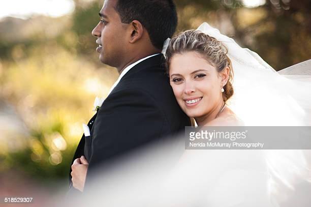 Bride hugging Groom with veil