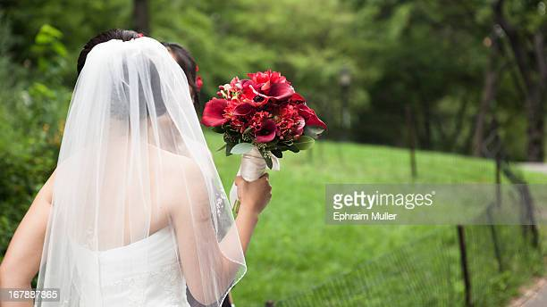 Bride in a veil central park holds a striking red boquete of roses