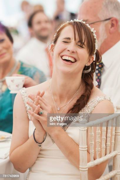 Bride in her wedding dress sitting in a marquee, hands clasped and laughing.
