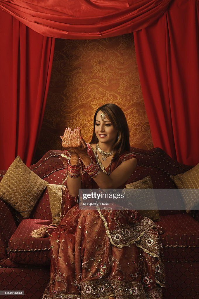 Bride in traditional wedding dress looking at henna decoration on her palms : Stock Photo