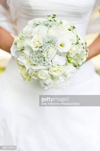 bride in wedding dress holds bridal flowers