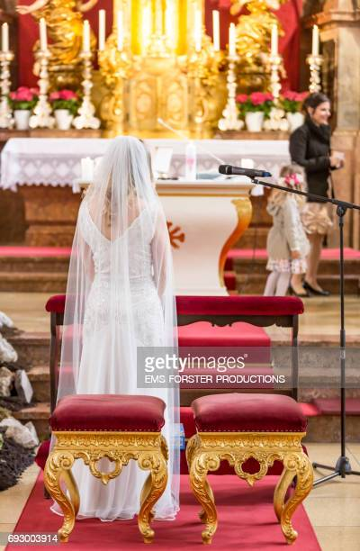 bride in wedding dress with train stands in front of the altar in a catholic church waiting for her groom and the wedding ceremony to begin