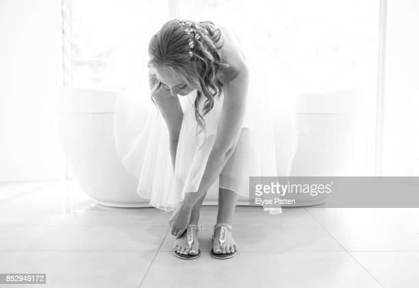 A bride is leaning over to buckle her casual shoes as the finishing touch to getting dressed for her wedding. She sits on a bathtub in front of a large window.