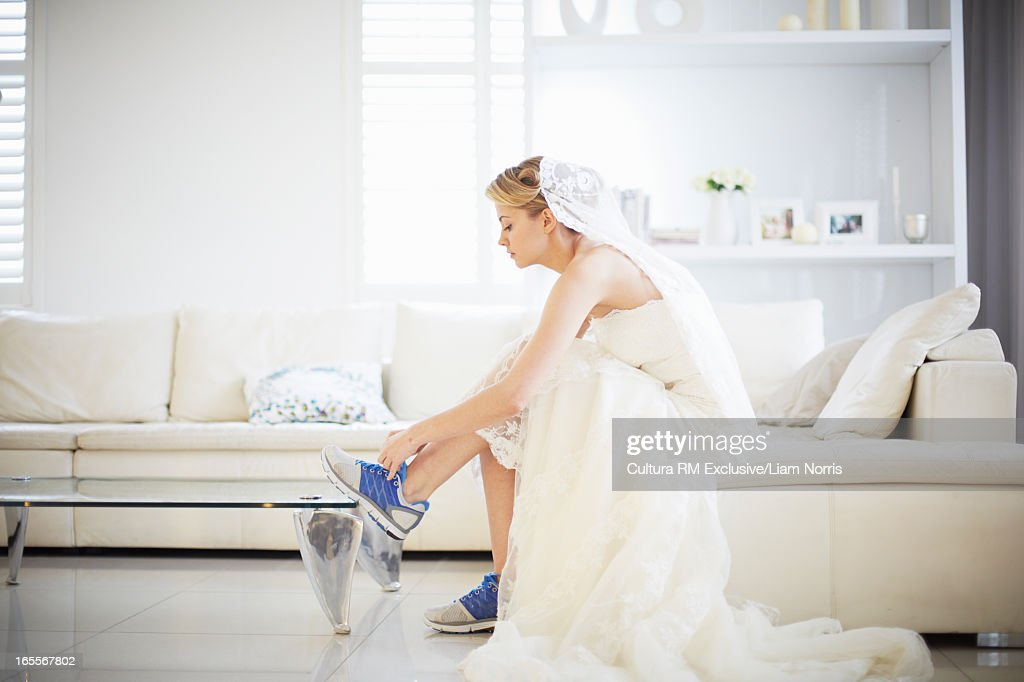 Bride lacing up running shoes : Stock Photo