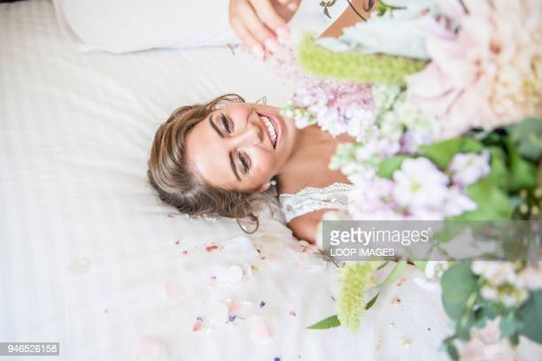 A bride laying on bed in her bridal suite whilst holding a bouquet of flowers