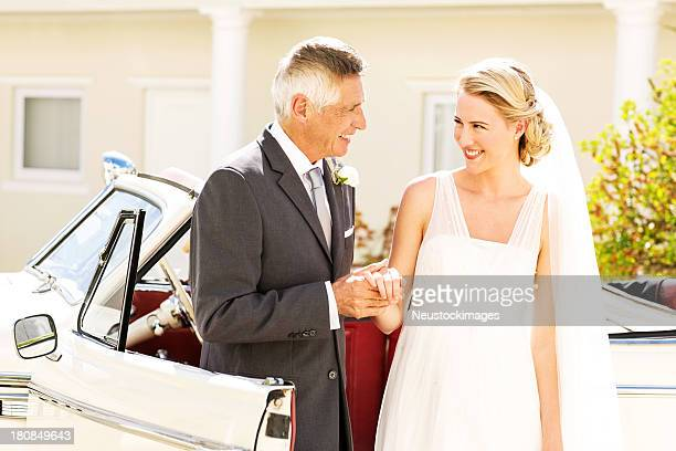 Bride Looking At Father While Standing By Wedding Car