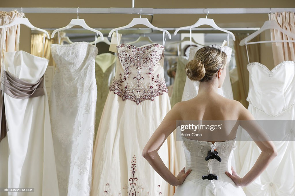 Bride looking at rack of dresses : Stock Photo