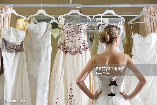 bride looking at rack of dresses - dress stock pictures, royalty-free photos & images